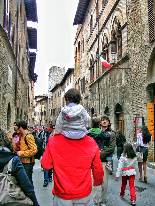 A baby riding on daddy's shoulder